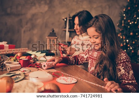 Adorable cute girl with mom doing handcraft activity, enjoying, desktop is full of materials. Happiness, upbringing, childhood, friendship, leisure, hobby, traditions x mas noel concept #741724981
