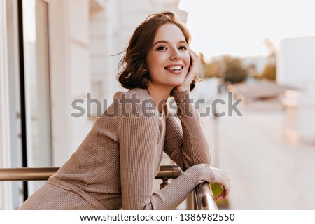 Adorable dark-eyed girl laughing at balcony. Photo of cheerful caucasian woman with beautiful smile.
