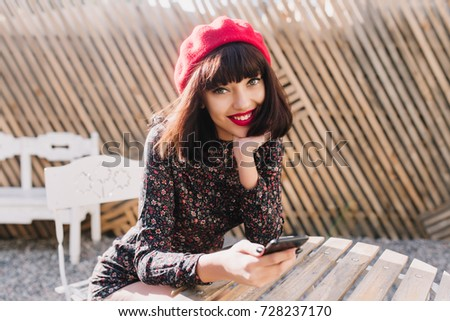 Adorable dark-haired girl waiting for friends in stylish outdoor cafe and checking new messages on black phone. Smiling brunette young woman with french vintage outfit resting in open-air restaurant stock photo