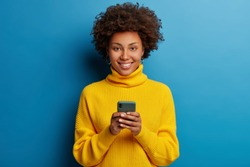 Adorable dark skinned adult woman dressed in yellow jumper, holds mobile phone, browses social networks, has broad smile, enjoys online chatting, isolated on blue wall, being always in touch