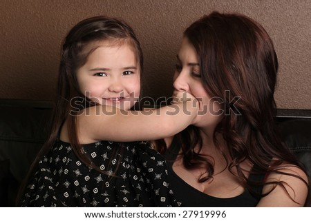 Adorable Daughter Covering Her Mothers Mouth in a Playful Way