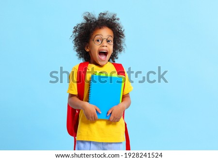 Adorable diligent little black schoolboy with Afro hair in casual clothes and eyeglasses screaming with astonishment while standing against blue background with notebooks Photo stock ©