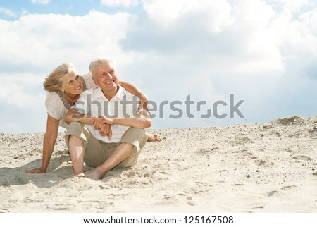 Adorable elderly couple went to the beach to enjoy the sea breeze