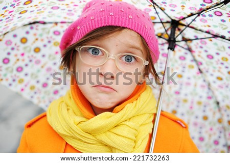Adorable, elegan sad school aged kid  girl wearing orange  coat, yellow scarf and pink hat, and boots holding colorful umbrella walking in the city street autumn  day