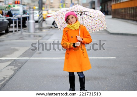 Adorable, elegant school aged kid  girl wearing orange  coat, yellow scarf and pink hat, and boots holding colorful umbrella walking in the city street autumn  day