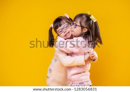 Adorable extraordinary children. Charming positive sisters with chromosome abnormality hugging each other and being extremely lovely #1283056831