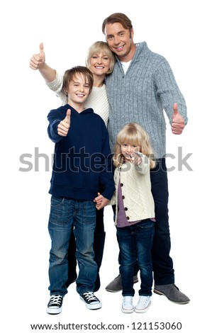 Adorable family in winter clothes gesturing thumbs up. Full length portrait over white background.