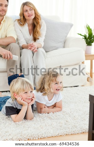 Adorable family watching tv in the living room