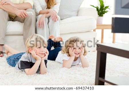 Adorable family watching tv in the living-room