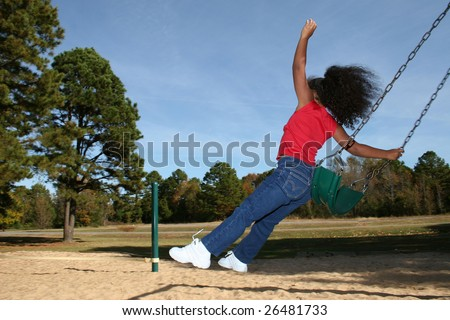 Adorable five year old African American Girl at park on swing.