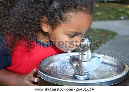 Adorable five year old African American Girl drinking from water fountain