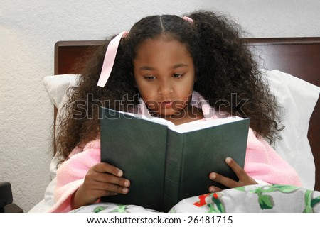 Adorable five year old African American Girl reading in bed.