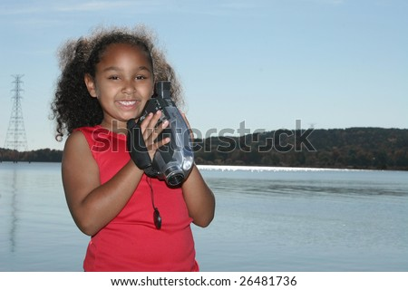 Adorable five year old African American Girl with camcorder at the lake.