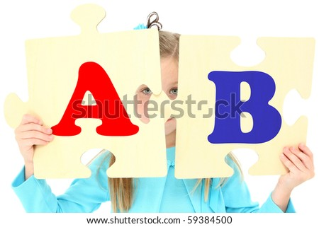 Adorable five year old american girl holding up large alphabet puzzle peaces over white background.