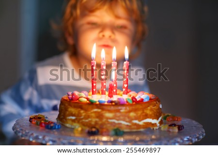 Adorable four year old kid celebrating his birthday and blowing candles on homemade baked cake, indoor. Birthday party for kids. Focus on child