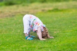 Adorable funny baby girl standing with her head down in a summer