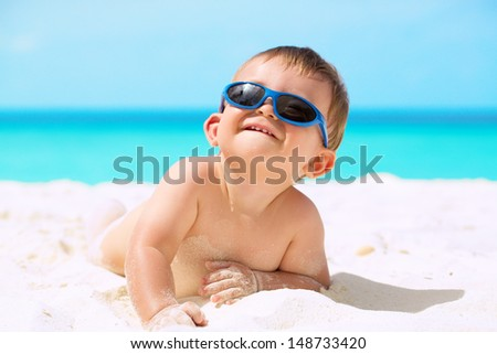 Adorable funny baby with sunglasses lying on the white sandy beach and enjoying his first tropical vacation at Maldives
