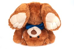Adorable funny fluffy brown teddy bear baby stuffed toy with small black plastic eyes and dark blue satin bow tie standing upside down on white background.