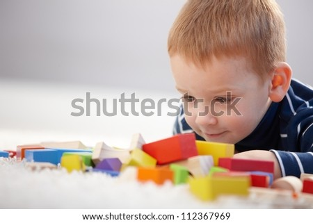 Adorable ginger-haired little boy playing with cubes, smiling.