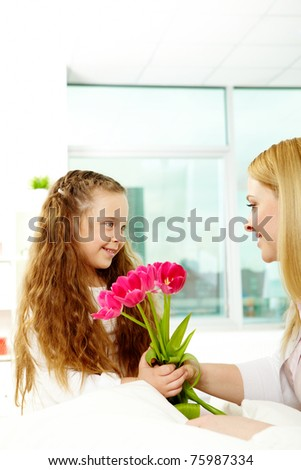 Adorable girl giving bunch of beautiful tulips to her mother