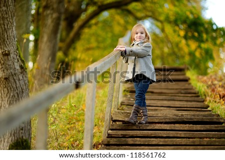 Adorable girl having fun on beautiful autumn day
