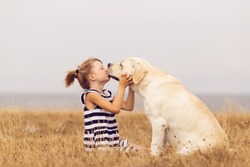 adorable girl hugging her labrador retriever. happy kid with big white dog outdoors. child and her dog best friend having fun in the garden. girl with cute family dog.