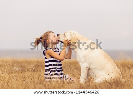 adorable girl hugging her labrador retriever. happy kid with big white dog outdoors. child and her dog best friend having fun in the garden. girl with cute family dog.  Zdjęcia stock ©