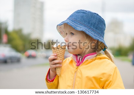 Adorable girl in blue hat eat ice cream on street