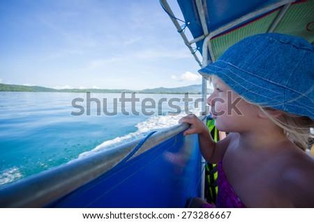 Adorable girl in blue hat on longtail boat in open ocean near islands