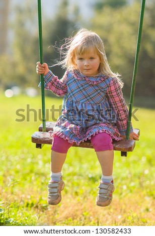 Adorable girl in dress swing on playground in park