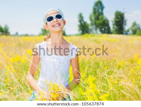 Adorable girl in glasses with flowers in yellow field. Summer freedom andjoy concept.