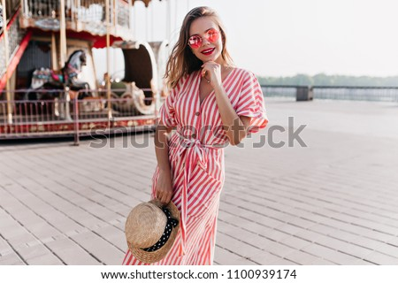 Adorable girl in long striped dress enjoying festive in amusement park. Outdoor photo of blissful female model with blonde hair holding straw hat. #1100939174