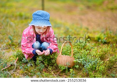 Adorable girl picking foxberries in the forest on summer day