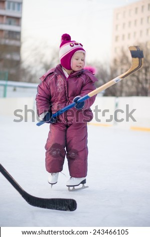 Adorable girl play with hockey stick in skates  on ice rink