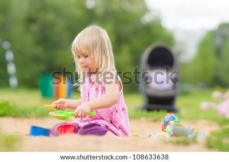 Adorable girl play with toys on sandbox