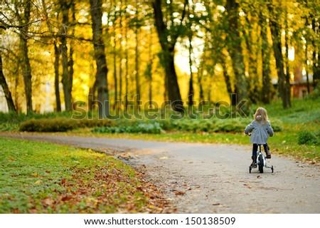 Stock Photo Adorable girl riding a bike on beautiful autumn day