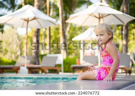 ef8558afff1e6 Adorable girl seat on pool side at tropical beach with legs in water.  Chairs and