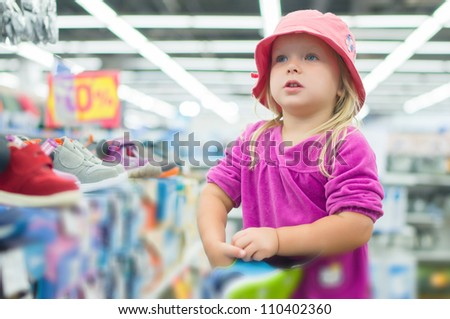 Adorable girl selecting shoes in supermarket