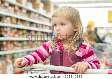 Adorable girl sit in shopping cart in supermarket