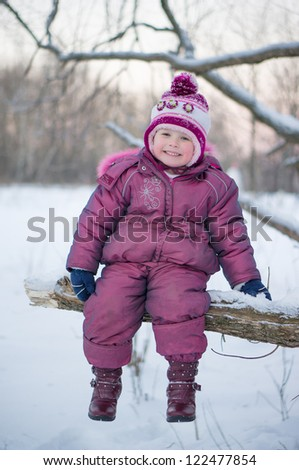 Adorable girl sit on huge tree branch and smile in winter park in evening