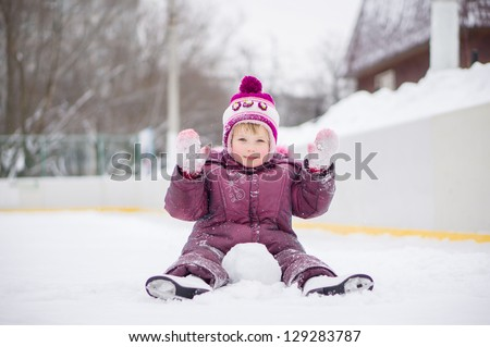 Adorable girl skate on ice rink, seat on ice covered with snow after fall and play with snow