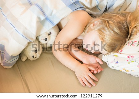 Adorable girl sleep in bed with plush seals toys