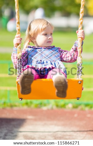 Adorable girl swing on playground near living building