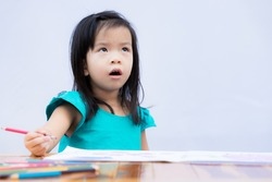 Adorable girl upset when she has to do hard homework. Cute child made a bored face and glanced on it. Kid doing homework on the table. Children 3-4 years old. Isolated white wall background.