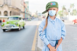 Adorable girl wearing a mask for prevent virus in the street with vintage classic american car in old Havana on Cuba.