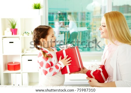 Adorable girl with big giftbox giving it to her mother