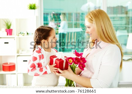 Adorable girl with bunch of beautiful tulips and giftbox giving them to her mother