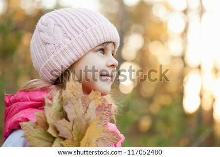 Adorable girl with leaves at autumn