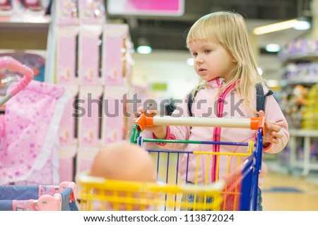 Adorable girl with small shopping cart in kids mall
