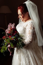 Adorable gorgeous happy bride holding big wedding bouquet, posing. Beautiful pretty woman smiling, excited about marriage. Attractive adult lady wearing stylish bridal white dress. High quality photo